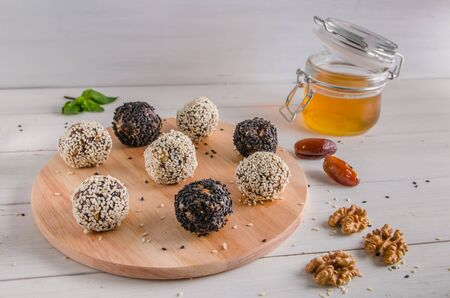 vegetarian food, homemade energy balls of walnuts, dates, prunes, cranberries and honey with white and black sesame on white background. Copy space Stok Fotoğraf