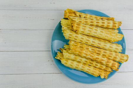 homemade waffle tubes on a blue plate on white background with copy space Imagens