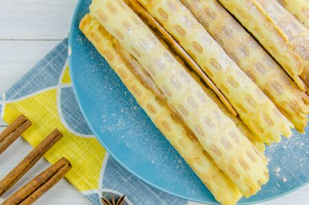 homemade waffle tubes on a blue plate on white background Imagens