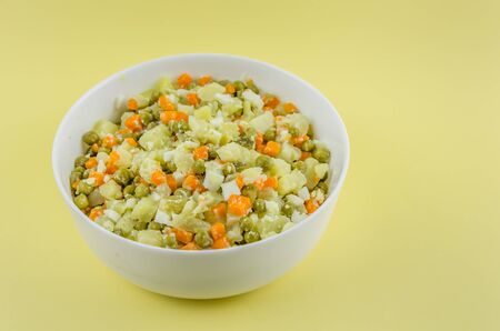 Russian salad Olivier with potato carrot green peas on yellow background with copy space