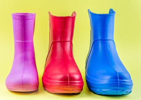 red blue and pink rubber boots EVA on a yellow background.
