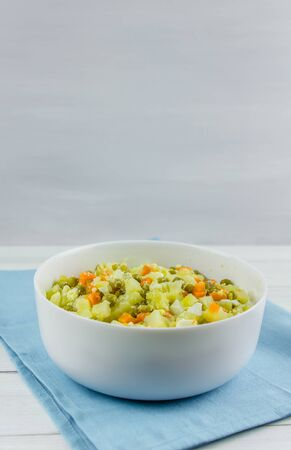 Russian salad Olivier with potato carrot green peas on white background