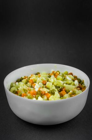 Russian salad Olivier with potato carrot green peas on black background