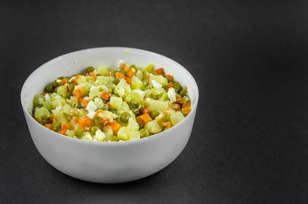 Russian salad Olivier with potato carrot green peas on black background with copy space