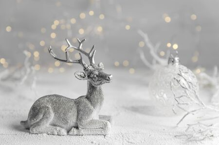 Christmas. New Years composition of silver deer and white New Years ball. garland lights. fairy forest