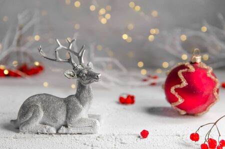 Christmas. New Years composition of silver deer and red christmas ball. garland lights. fairy forest