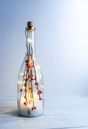 Christmas bottle with lights on a white background with copy space