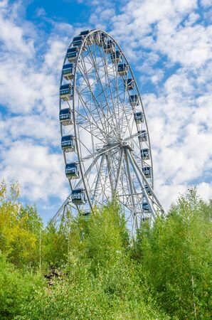 Ferris wheel against the blue sky with clouds