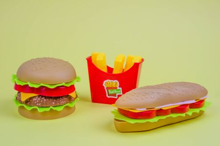 fast food. plastic hamburger, hot dog and french fries on a yellow background
