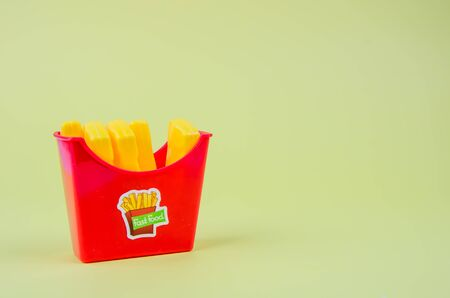fast food. plastic french fries on a yellow background. copy space. horisontal