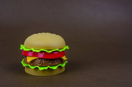 fast food. plastic hamburger on a brown background. copy space