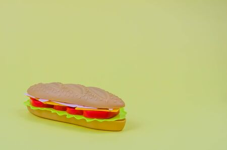 fast food. plastic hot dog on a yellow background. copy space Фото со стока