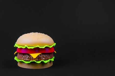 fast food. plastic hamburger on a black background. copy space Фото со стока
