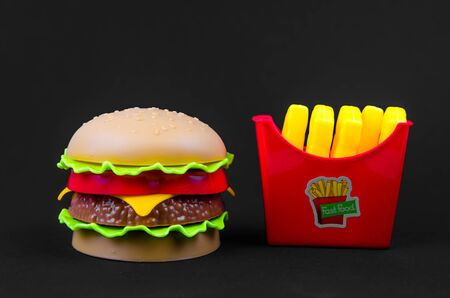 fast food. plastic hamburger and french fries on a black background