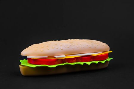 fast food. plastic hot dog on a black background 스톡 콘텐츠