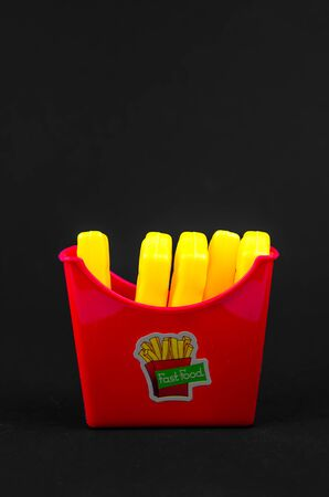 fast food. plastic french fries on a black background. copy space. vertical Фото со стока