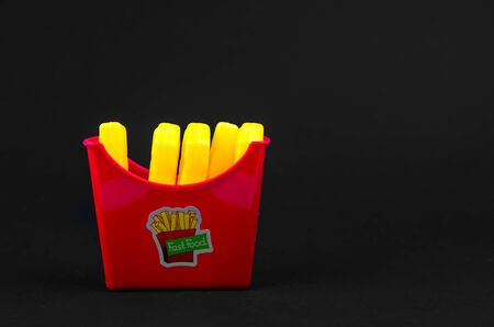 fast food. plastic french fries on a black background. copy space. horisontal
