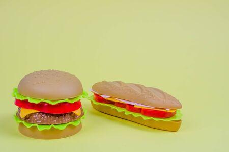 fast food. plastic hamburger, hot dog on a yellow background