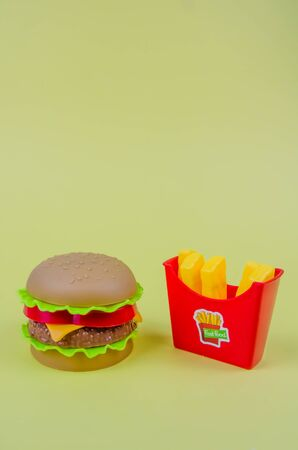 fast food. plastic hamburger and french fries on a yellow background Фото со стока