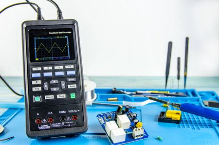 The electrician's workplace. Electronics. Schemes soldering iron. oscilloscope