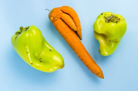 ugly food. green peppers and carrots on a blue background. copy space
