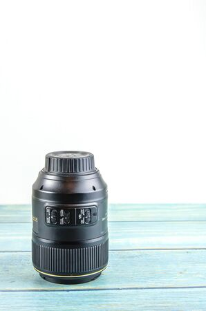 camera lens on a blue wooden background. copy space