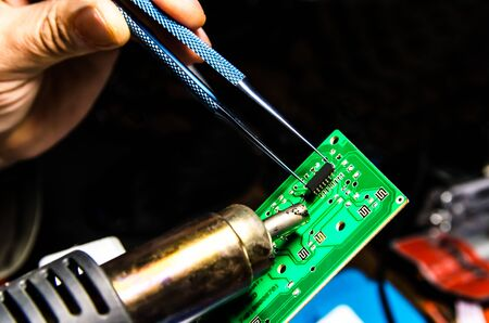 Technical support worker drops the fee PCB. Soldering iron. Tweezers Banco de Imagens - 132233062