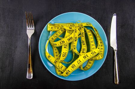 Top view of measuring tape on the plate. Diet concept