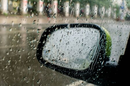 side mirror of the car mobolism in the rain. drops, glass, road