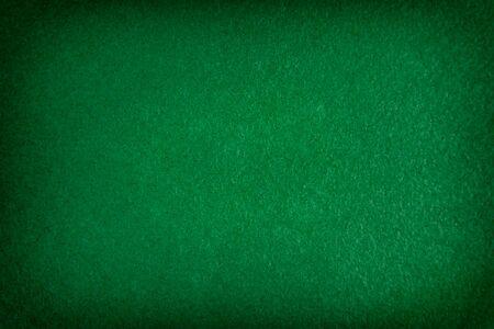 Dunkelgrüner matter Hintergrund aus Wildleder, Nahaufnahme. Textur aus nahtlosem smaragdgrünem Wollfilz mit Vignette. Standard-Bild