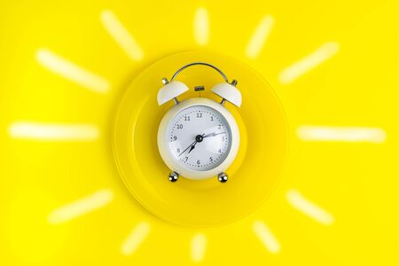 concept good morning alarm clock on a yellow plate with painted sunlight Фото со стока
