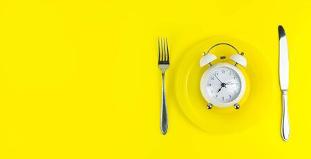 Alarm clock with fork and knife on the light yellow background. Time to eat, Breakfast, Lunch Time and Dinner concept. Copy space, banner