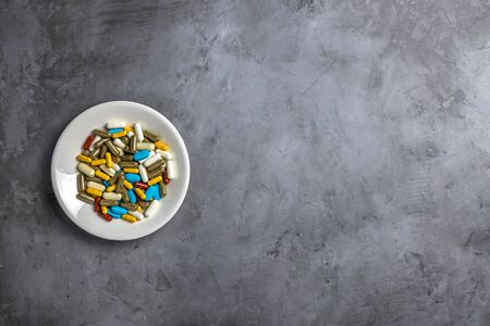 A variety of pills in a white plate on a gray concrete background. with copy space. pharmacy, medical background Banque d'images - 143278565