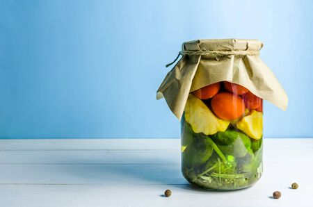 pickled vegetables. cucumbers, tomatoes, patissons on blue background with copy space Reklamní fotografie