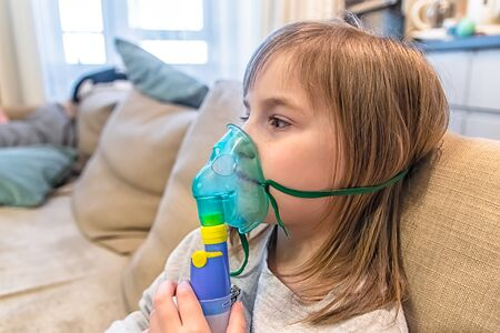 Cute baby girl breathes through nebulizer inhaler. health
