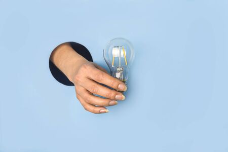 Hand holding a light bulb breaking through the hole in blue background