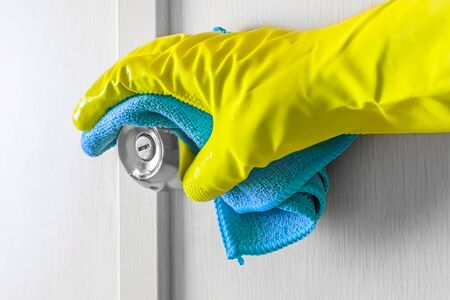 Employees hand in rubber protective glove with rag wiping a wooden door. Zdjęcie Seryjne