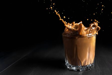 Splash of ice coffee drink on a brown background. cup with ice cubes. Cold beverage wave. Close-up design liquor milk, coffee and ice.