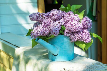 beautiful bouquet of lilacs in blue garden watering