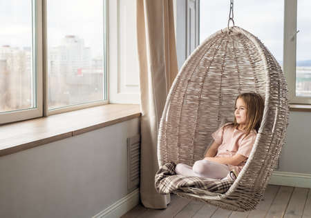 Cute girl sits in a hanging chair and looks out the window Banco de Imagens