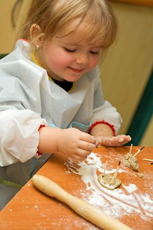 girl having fun with the cookie leftovers in the kitchen Stock Photo - 2753418