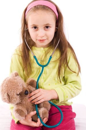 Adorable little girl playing doctor with a teddy bear - studio shot - isolated Stock Photo - 2753422