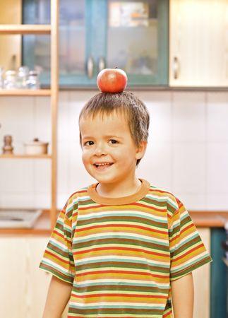 Cute boy balanced a red apple Stock Photo - 2791779