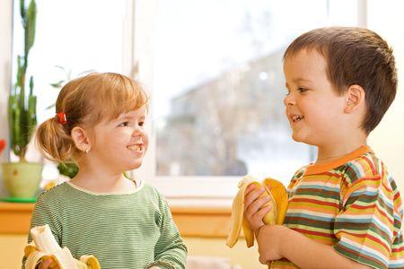 Happy little girl and boy eating bananas Stock Photo - 2791790