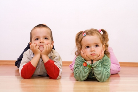 Two kids bored, looking at something - laying on the floor Stock Photo - 2880519