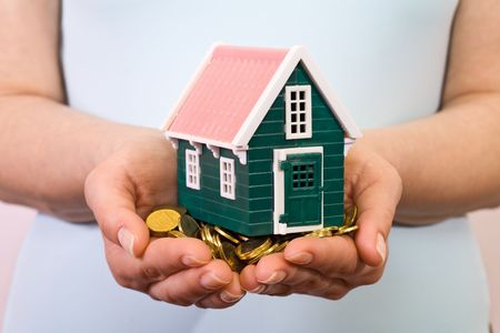 pile dwelling: House on a pile of golden coins in woman hands Stock Photo