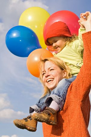 Happy mother and cute child playing with balloons Stock Photo