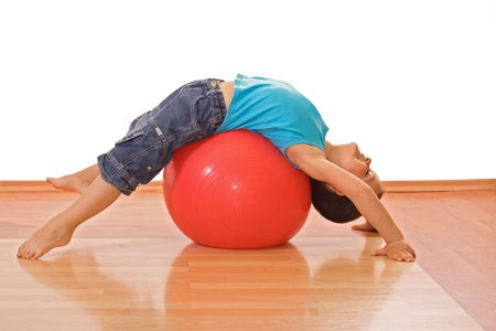 ball stretching: Happy little boy stretching on a gymnastic ball - isolated Stock Photo