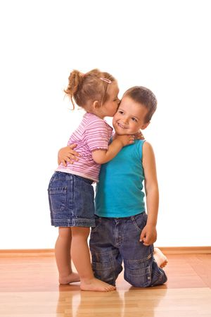 kneeling woman: Little girl kissing her older brother on the cheek - isolated