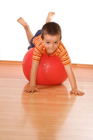 exhilarating: Little boy playing with a huge red gymnastic ball